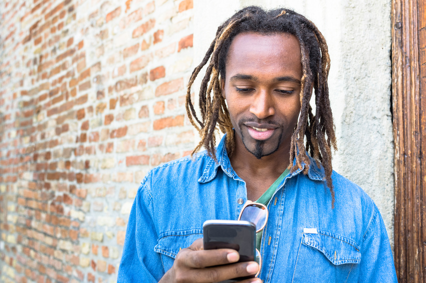 African american young man using mobile smart phone - Hipster guy texting on social media with smartphone device