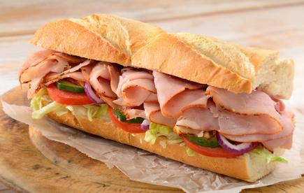 Ham and salad submarine sandwich from freshly cut baguette on rustic wooden bread board.