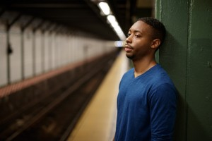 Young man in city at subway platform tired