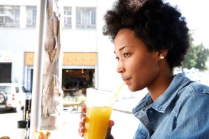 Portrait of fashionable young african woman sipping orange juice