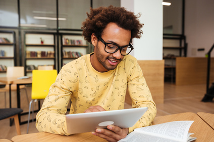 Happy african american young man in glasses learning and using tablet in library