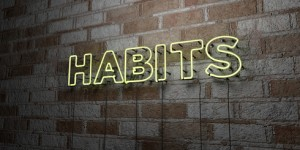 HABITS - Glowing Neon Sign on stonework wall - 3D rendered royalty free stock illustration. Can be used for online banner ads and direct mailers.
